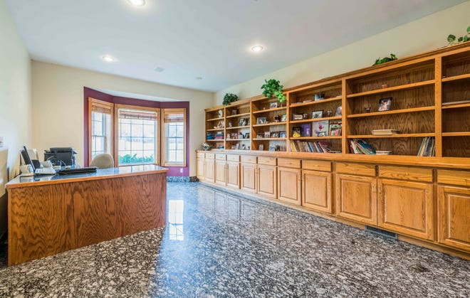 A main floor office features a full wall of built-in bookcases and cabinets for a multitude of storage and organization.
