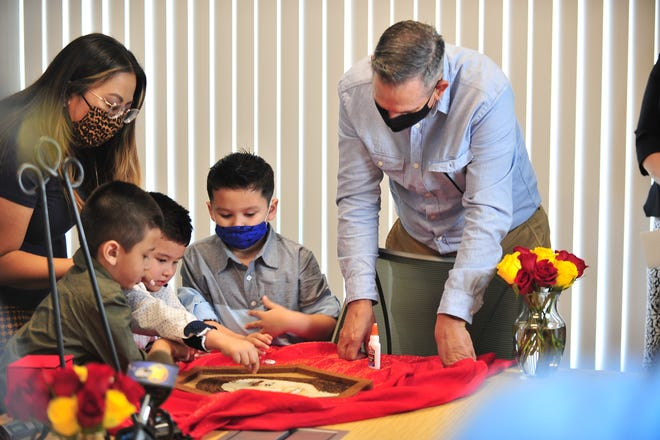 Hanah Salazar, her children and husband, John Blakely, work on a floragraph for their daughter, Francine, who passed away at age 10.