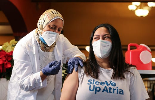 Marie Branham, right, resident services director at Atria Springdale assisted living community, receives the Pfizer coronavirus vaccine from CVS pharmacist Shereen Keshta at the facility in Louisville, Ky. on Dec. 21, 2020.