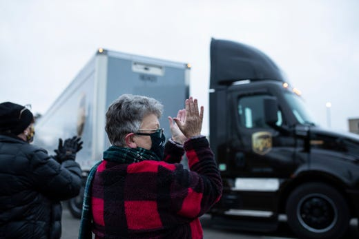 Susan Deur of Plainwell, center, and Nancy Galloway of Plainwell, applaud and cheer as they watch the trucks carrying COVID-19 vaccine leave at Pfizer Global Supply in Portage, Mich., Dec. 13, 2020.