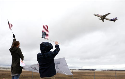 Courtney Schneider, 40, of Grand Rapids and her son, Elliot Schneider, 8, of Grand Rapids wave flags at the FedEx plane carrying the Pfizer COVID-19 vaccine at the Gerald R. Ford International Airport in Grand Rapids, Mich. on Dec. 13, 2020.
