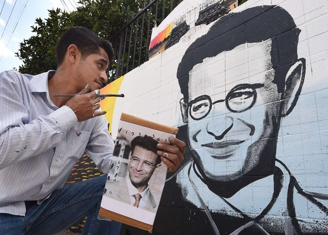 Artist Levi Ponce poses with his Memorial Day mural project of murdered journalist Daniel Pearl, near his old neighborhood in Los Angeles, California on May 23, 2015. Pearl was a Wall Street Journal reporter who was kidnapped and murdered by a terrorist group in Pakistan in 2002 while doing an investigative story. The artist is working with students from the Daniel Pearl High School and LAPD West Valley Police cadets on the project.