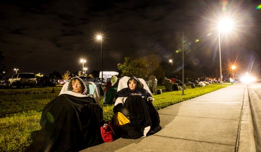 Friends Terri Kado,66, right and Patty Tubbs,68, from Fort Myers Beach wait in line for the the COVID-19 vaccine in the early morning hours of Dec. 30, 2020 at Lakes Park Regional Library in Fort Myers, Fla. The two were having a pleasant experience and were watching the moon as it moved through the sky. To them the vaccine brings a peace of mind and a positive start to the New Year. They got in line at 12:00 a.m. on Wednesday.