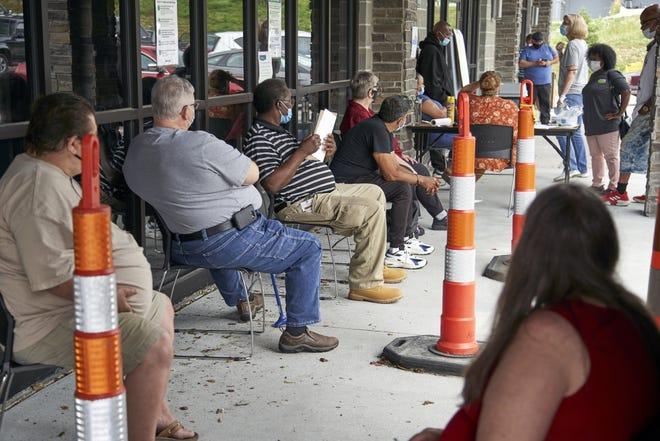 Job seekers, shown here in July, exercise social distancing as they wait to be called into the Heartland Workforce Solutions office in Omaha, Neb. A second round of COVID relief is poised to affect the finances of millions of Americans. [AP PHOTO/NATI HARNIK/FILE]