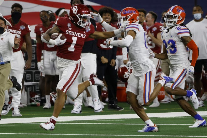 Oklahoma running back Seth McGowan fights off a tackle attempt by Florida defensive back Donovan Stiner during the Sooners' 55-20 blowout win in the Cotton Bowl on Wednesday night. Oklahoma rushed for 452 yards and averaged 10.52 yards per play in the rout.