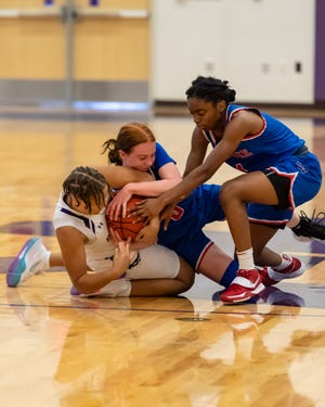 Jakayla Thompson, left, of Cedar Ridge fights for a loose ball with Peyton Feiermuth, center, and LaQuayla Chambers-Wells of Westlake. Cedar Ridge won a girls nondistrict basketball game at home over Westlake 55-48 on Dec. 30.