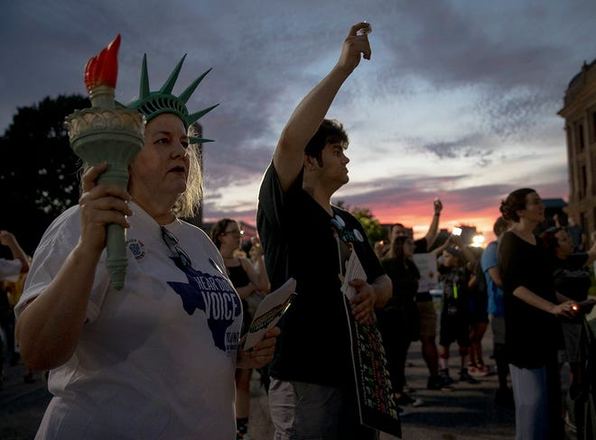 "Julie Reichert, left, and her son, Ben, shown in 2019, join a ""Lights for Liberty"" vigil in Austin to call attention to the treatment of immigrants in detention centers. [NICK WAGNER/AMERICAN-STATESMAN]"