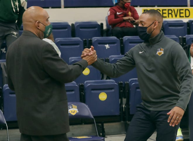 St. Vincent-St. Mary head coach Dru Joyce, left, shakes hands with his son Cam, St. Ignatius head coach, after the Irish's 50-40 win on Thursday, Dec. 31, 2020 in Cleveland, Ohio.  [Phil Masturzo/ Beacon Journal]