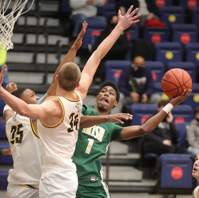 St. Vincent-St. Mary's Sencire Harris puts up a first quarter shot as St. Ignatius' Shondo Green, Jr., left, and Will Yontek defend on Thursday, Dec. 31, 2020 in Cleveland, Ohio.  The Irish won the game 50-40. [Phil Masturzo/ Beacon Journal]