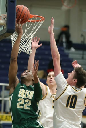 St. Vincent-St. Mary's Malali Branham drives past St. Ignatius Will Yontek and Henry Raynor for a third quarter basket on Thursday, Dec. 31, 2020 in Cleveland, Ohio.  The Irish won the game 50-40. [Phil Masturzo/ Beacon Journal]