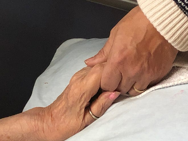 Reporter Craig Webb holds the hand of his mother, Janet, just before she died after contracting the coronavirus.