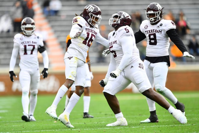 Texas A&M defensive back Brian George (16), and defensive linemen Bobby Brown III and DeMarvin Leal (8) celebrate against Tennessee during a game in Neyland Stadium in Knoxville, Tenn., Dec. 19.