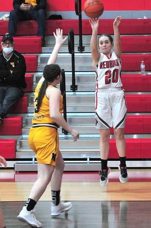 Loudonville's Shalen Guilliams (20) puts up a shot over Northmor's Regan Swihart (3) during the Redbirds' 85-32 win Wednesday at Loudonville High School.