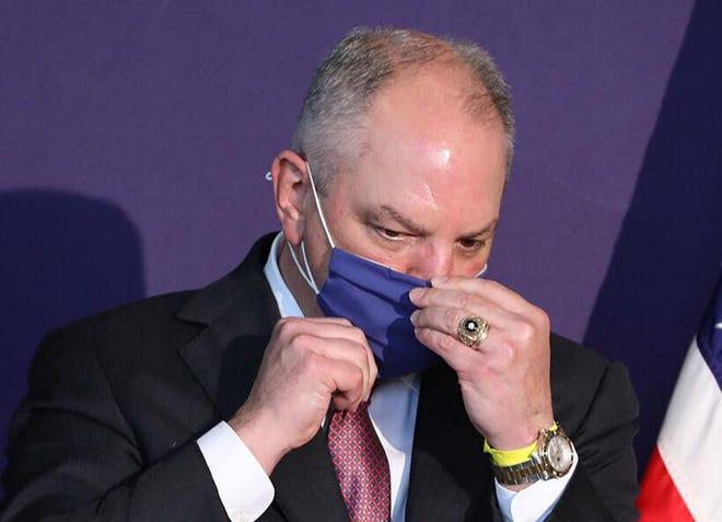 Gov. John Bel Edwards puts on a face mask.