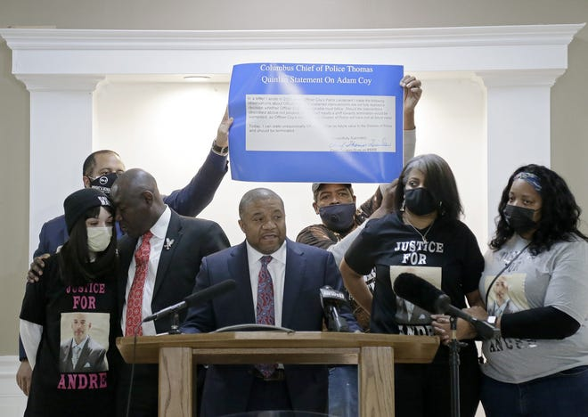 Attorney Michael Wright speaks as Ben Crump comforts Andre Hill's daughter, Karissa Hill, while a statement made by Columbus Chief of Police Thomas Quinlan in reference to complaints about police officer Adam Coy is held up during a press conference on Thursday.