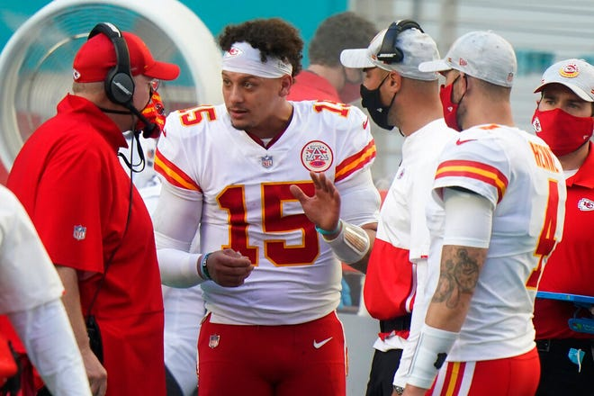 Kansas City Chiefs quarterback Patrick Mahomes (15) and Chad Henne (4) talk to head coach Andy Reid on the sidelines, during the second half against the Miami Dolphins, Dec. 13, in Miami Gardens, Fla. (AP Photo/Wilfredo Lee)