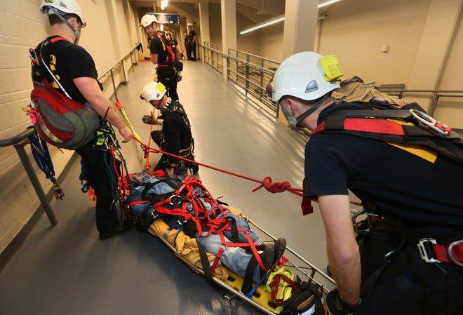 Hutchinson Fire Dept. firefighters Trey Markhams, right, Caleb Miller, left, Brent Fisher, center, and Mike Sooter, top, work together to rescue a training dummy in a stokes basket during a training scenario at the Sports Arena Wednesday.
