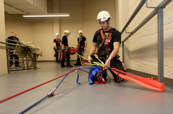 Hutchinson Fire Dept. firefighter Mike Sooter adjusts the ropes used in a low-angle rescue scenario at the Sports Arena Wednesday morning, Dec. 30, 2020.