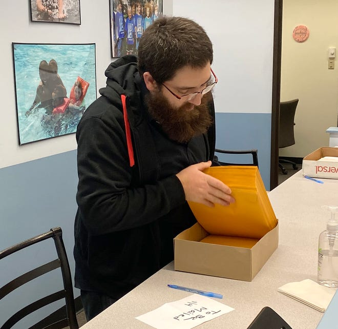 City parks and recreation Recreational Leader Jonathan Bagg prepares activity packets that will be distributed to city senior citizens.