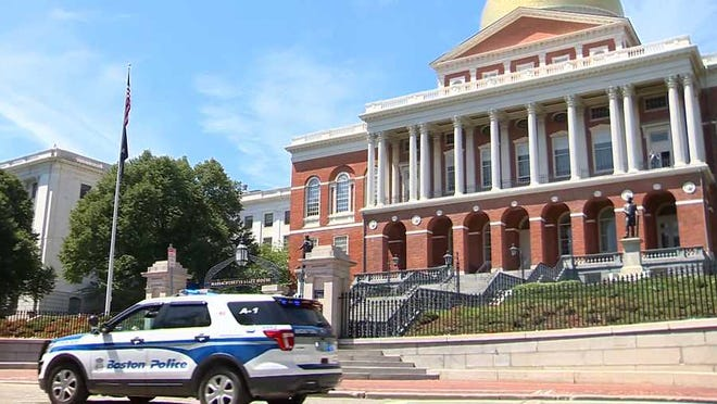 A Boston police cruiser is parked outside the State House. Gov. Charlie Baker on Thursday signed into law a police reform bill.