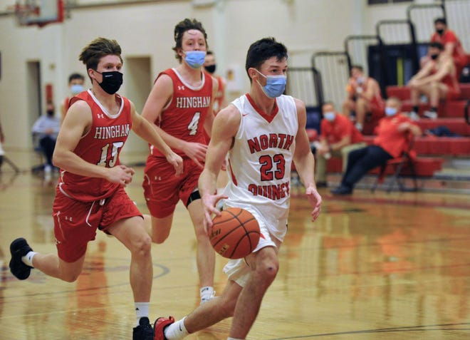 North Quincy's Colm Geary, right, is pursued by Hingham's Evan Williams, left, and Nick Johannes during boys basketball action at North Quincy High School, Wednesday, Dec. 30, 2020.