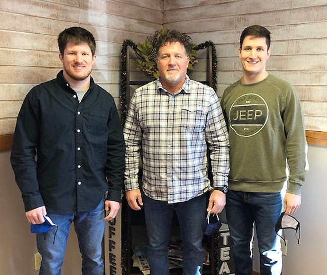 Rod Hoselton, middle, stands with son Andy, left, and Brad inside Crossroads Cafe during an event honoring the late Mari Lynn Hoselton, wife of Rod and mother to Andy and Brad last weekend.