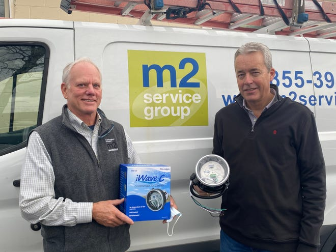 Steve Sewall (left), president of m2 Mechanical, and Steve Klatt (right), the company's HVAC division director, hold up the patented iWave air purification device. The iWave is installed in HVAC system and adds positive and negative ions into incoming air to neutralize pathogens.