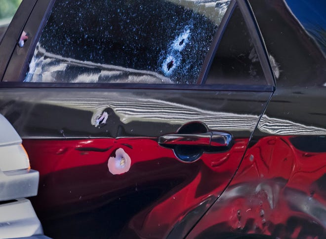 A car found at the Coronado Springs apartment complex in Palm Springs with a male inside who had been shot to death is seen riddled with bullet holes as it is towed away Thursday morning, January 9, 2020. [LANNIS WATERS/palmbeachpost.com]