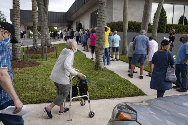 Seniors stand in line to make an appointment to receive the Moderna COVID-19 vaccine outside the Kings Point clubhouse in Delray Beach,  Fla., on Wednesday, Dec. 30, 2020.