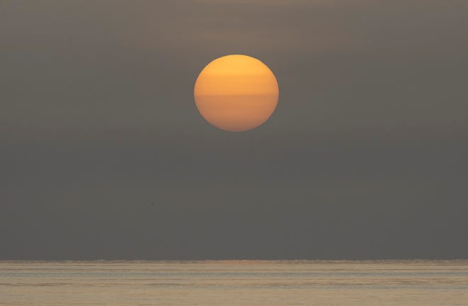 A dusty Saharan sunrise over Palm Beach June 30, 2020.