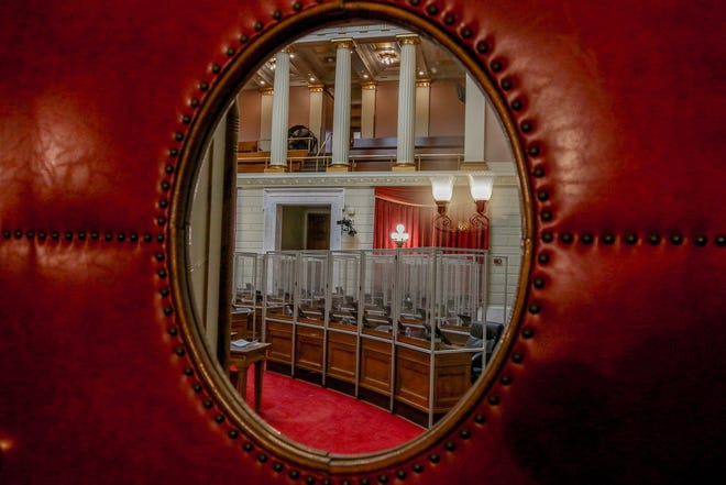 The empty House chamber, with seats separated by plexiglass partitions, is seen through a door window at the State House. The House will convene this week at Veterans Memorial Auditorium.
