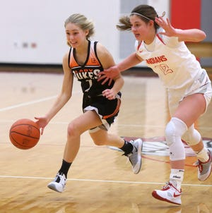 Maria Warner (left) of Marlington brings the ball up court while being defended by Gianna Kuhn (12) of Northwest during their game at Northwest on Wednesday, Dec. 30, 2020.