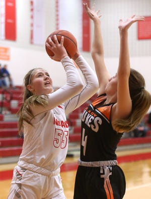 Lily Bottomley (55) of Northwest takes a shot while being defended by Lexi Miller (4) of Marlington during their game at Northwest on Wednesday.