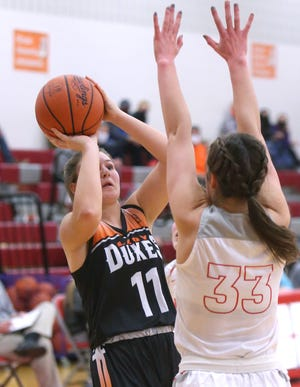 Chelsea Evanich (11) of Marlington takes a shot while being guarded by Jordan Marecek (33) of Northwest during their game at Northwest on Wednesday, Dec. 30, 2020.