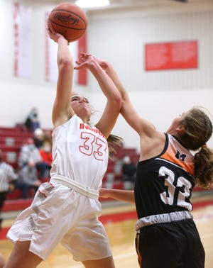 Jordan Marecek (33) of Northwest takes a shot while being defended by Elizabeth Mason (32) of Marlington during their game at Northwest on Wednesday, Dec. 30, 2020. Marecek was fouled on the play.
