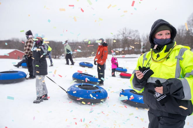 Patricia Larson, a Tube Hill Crew member, and snow tube hill participants are showered in confetti at midday during the Noon Year's Eve Celebration at Snow Park at Alpine Hills on Thursday, Dec. 31, 2020, in Rockford.