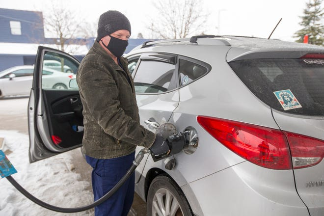 Jeff Jenke of Sycamore, who works in Rockford, pumps gas at Circle K, 3819 Broadway, on Thursday in Rockford. Gas prices are expected to rise in the new year as the rollout of the COVID-19 vaccine continues.