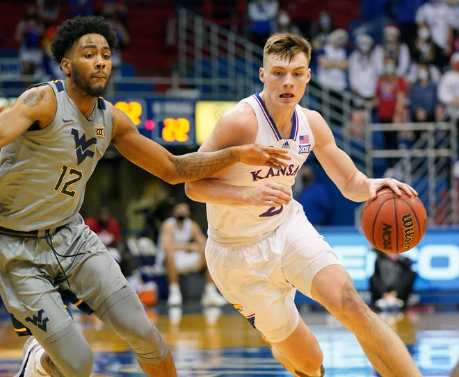 Kansas basketball's Christian Braun dribbles the ball past West Virginia's Taz Sherman during last Tuesday's game at Allen Fieldhouse in Lawrence. Braun scored a team-high 22 points with seven assists in the No. 3-ranked Jayhawks' 79-65 victory.