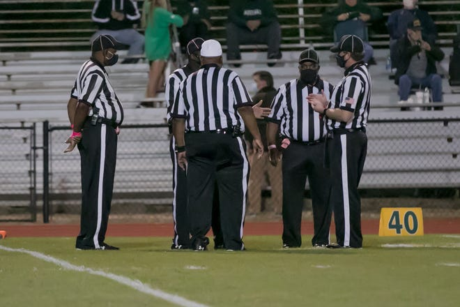 Game officials  review assignments prior to the start of a high school football game between Aquinas and host Savannah Country Day on Oct. 30, 2020.