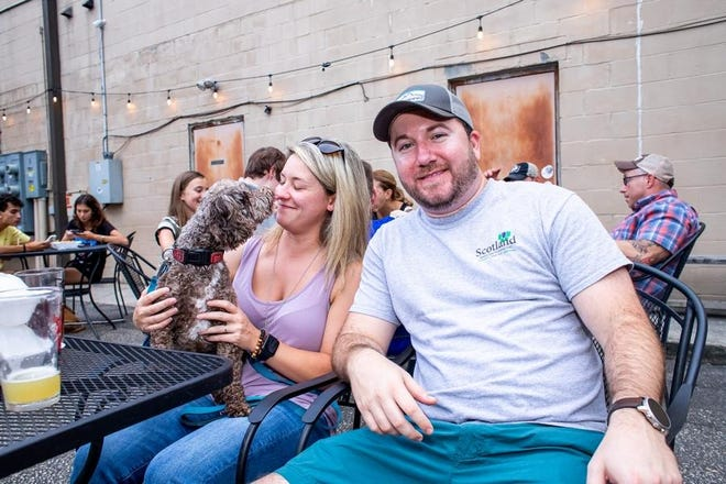 Jessie, Matt and their dog Teddy have drinks on the patio at Bright Light Brewing Co. in July 2019.