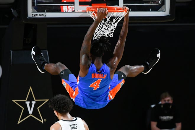 Florida forward Anthony Duruji hangs from the rim after a dunk during the first half Wednesday against Vanderbilt in Nashville, Tenn.