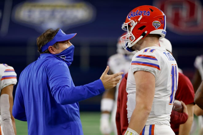 Florida coach Dan Mullen talks with quarterback Kyle Trask after Trask threw a pass into the end zone that was intercepted by Oklahoma's Woodi Washington during the first quarter of the Cotton Bowl in Arlington, Texas on Wednesday.