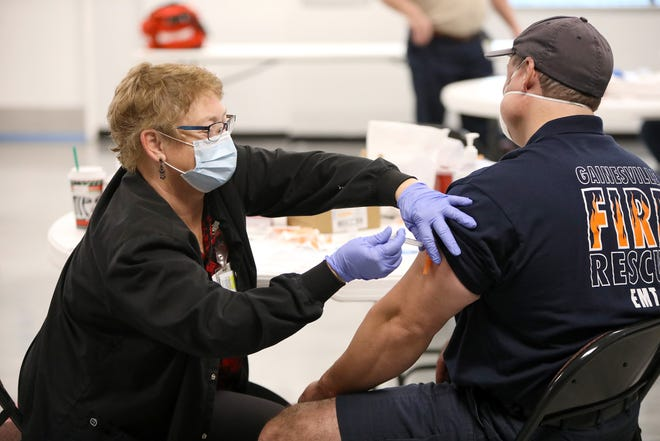 A nurse with the Alachua County Health Department administers a dose of the Moderna COVID-19 vaccine during a vaccination session for local firefighters at the Gainesville Professional Firefighters Union Hall in Gainesville on Dec. 31.