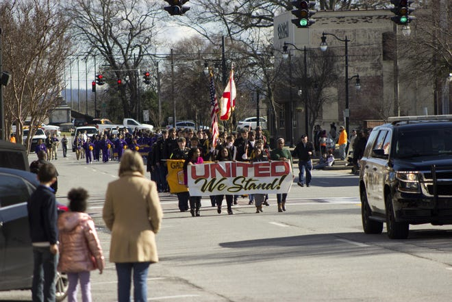 """Students marching with a """"United We Stand"""" banner lead the sixth annual Unity in the Community/MLK Day Parade on Broad Street on Jan. 24, 2020. The 2021 parade has been called off because of COVID-19 concerns."""