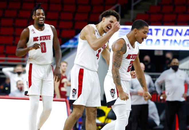 North Carolina State's D.J. Funderburk (0), Jericole Hellems (4) and Shakeel Moore (2) celebrate after the team's victory over Boston College in an NCAA college basketball game in Raleigh, N.C., Wednesday, Dec. 30, 2020. (Ethan Hyman/The News & Observer via AP, Pool)
