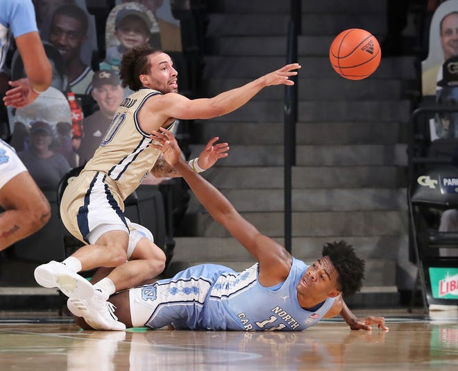 Georgia Tech guard Jose Alvarado comes away with a steal against North Carolina forward Day'Ron Sharpe, bottom, during Wednesday night's game.