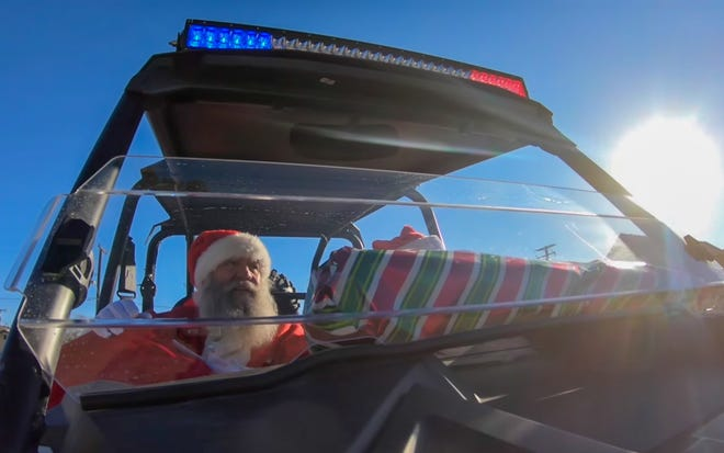 Santa Claus rides in a sheriff's UTV on Christmas morning, Dec. 25, 2020.