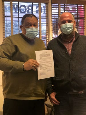 Dr. O'dell Owens and Walton Mayor Gabe Brown meet Thursday morning inside Frisch's in Covington with a deed for the 54-acre property Owens donated to the city for use as a park.