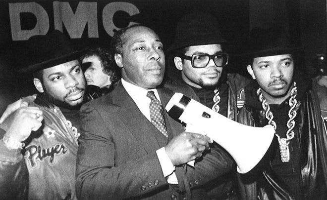 Dalam file foto 11 Februari 1988 ini, Joe Clark, kepala sekolah Eastside High School di Paterson, NJ, berdiri bersama grup rap Run-DMC sebelum grup tersebut mengadakan konser di sekolah untuk mendukung cara Clark menjalankan sekolahnya.
