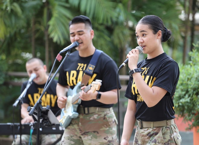 Specialist Syd Refugia, right, belts a song, backed up by Spc. Christopher Bolus and Staff Sgt. William Cunningham III. The Guam National Guard's 721st Army Band gave a holiday performance for guests in the COVID-19 quarantine facility at the Dusit Thani Beach Resort.